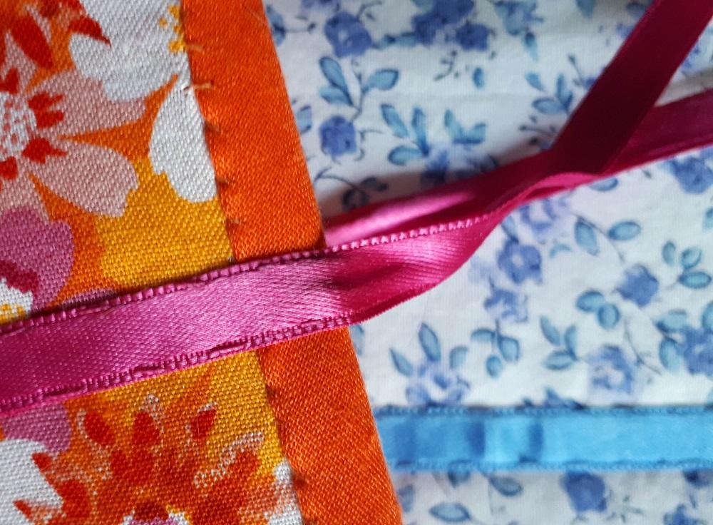 Détail des coutures à la main pour le biais et le ruban de satin.